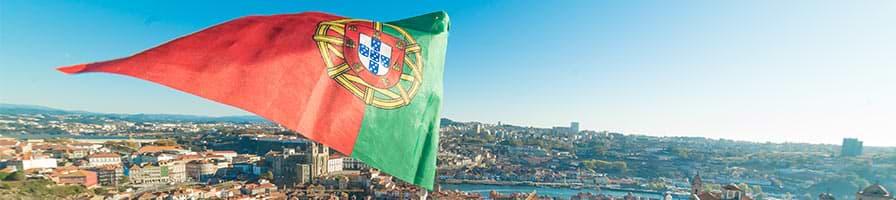 Flagge von Portugal, die über einer Stadt schwebt